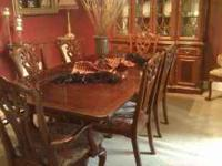 This is a formal dining room table with 8 chairs and a