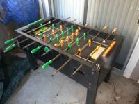 Full sized, neon colored, black light foosball table.