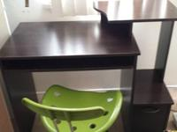 Small desk, green swivel chair, and set of shelves with