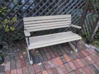 This garden bench is in the park bench style. The wood
