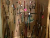 Collection of gardening tools, mostly hand tools,