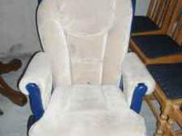 Blue glider rocker with cream colored cushions. Has a