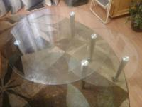 It is a round glass table that has a smaller table on a