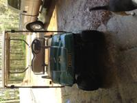 Green Ezgo golf cart, electric. Added windshield, all