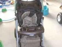 Brown and green Graco Stroller. Collapses to make it