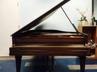 Brown grand piano by Baldwin Good condition, tuned.