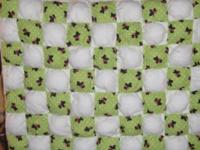 A homemade baby puff quilt size 31x38. It is green with