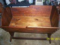 IT IS A HAND MADE CRADLE MADE OUT OF OAK WOOD AND IT IS