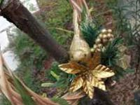 This 9 inch reed wreath features a golden bird nestled