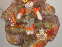Scarecrow doll is the center of this fall wreath,