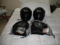Two Harley Davidson helmets. One XL the other Small.