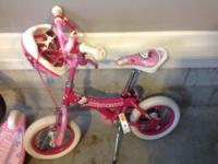 A white and pink Hello kitty bike . It is made for