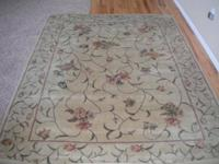 This is a tan floral rug with a greenish shade. The