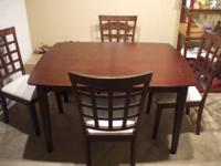 A rich dark wood dining table with 4 chairs with plush