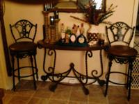 Two black wrought iron bar stools with swivel leather