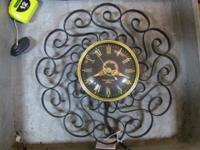 Mid mod clock with swirling iron ornamentation.