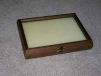 This is a jewelry display case made of dark wood and