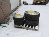 Tires and wheels off a John Deere 755 compact tractor.