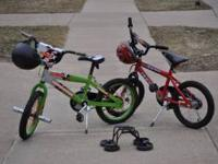 Two kids bikes, helmets, and training wheels in very