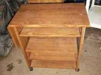 This is a wooden kitchen cart with wheels on the