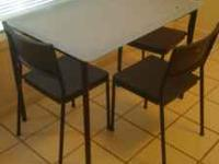 Small glass top kitchen table with 3 matching chairs.