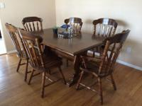 Dark wood dining table with two removable leafs, sits