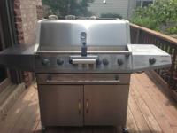 Large stainless steel gas grill with side burner. 4
