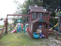 large wooden playset slide, swings, rock wall, see saw,