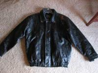 Large black leather jacket with silver snaps. Maxam