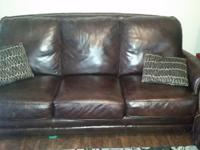 Brown leather sofa and love seat with nail head trim in