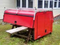 Leer red aluminum utility truck cap with ladder racks.