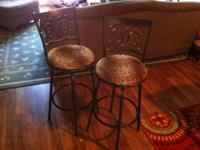 These are two dark-brown, metal bar stools with