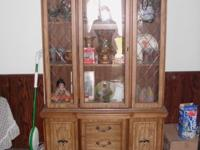 Light colored brown wood lighted china cabinet with