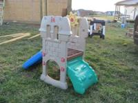 Has rock wall climbing on one side and slide on other,