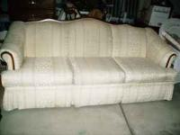 Formal living room couch; cream colored, with cherry