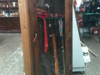 Tall Narrow glass front, dark wood gun cabinet with
