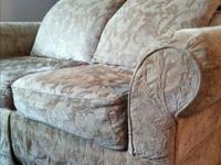 Tan love seat with pattern in material. Feels like
