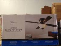 "A Mainstays 42"" ceiling fan w/ light. It has a bronze"