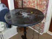 Beautiful table has a thick, heavy black iron bas with