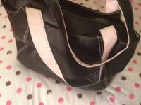 Black and pink tote bag with zipper and inside pocket.