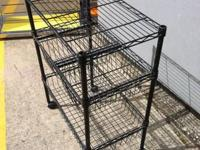 This is a metal kitchen rolling cart with racks and