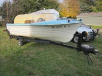 "16'  9""   MFG Fiberglass Boat with drive on trailer."