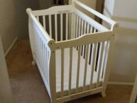 White mini crib. Sleigh style.  Includes mattress.