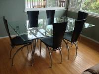 Modern glass dining room table with 6 black chairs.