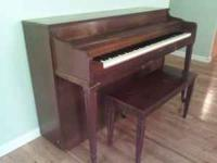 Old, wooden upright piano with matching bench.