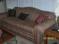 Sofa is striped-light gold, green, maroon and brown -
