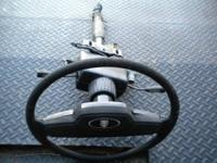 A used tilt steering column with black wheel, horn pad