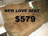 New Brown Reclining Love Seat for $579.   SITUATED IN