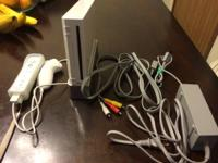 White Nintendo Wii with stand and one controller for