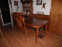 Oak dining room table with four chairs and one leaf.